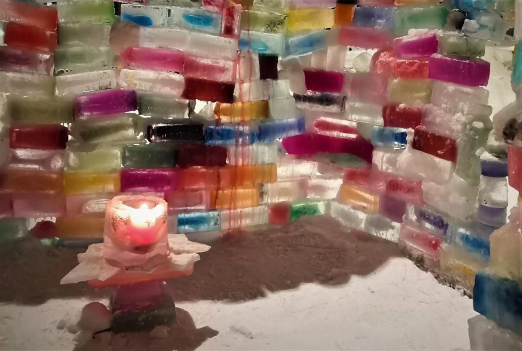 Kuvassa on värikkäistä jäätiilistä rakennettu linna, jonka sisällä palaa jäälyhty.