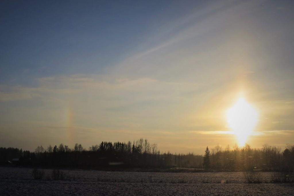 Kuvassa on talven valoilmiö, jossa auringon kanssa on vierekkäin on pilarimainen sateenkaari.
