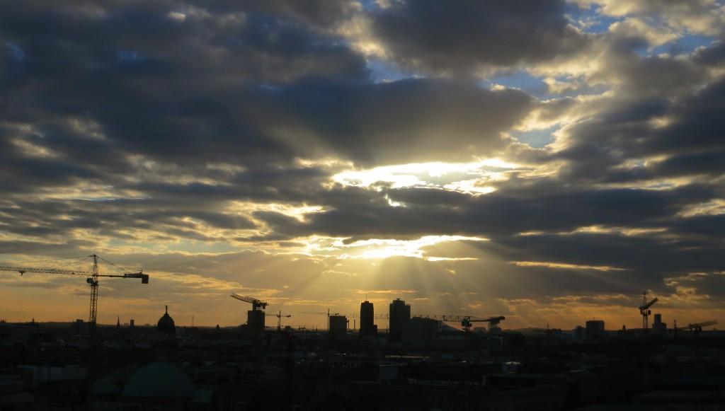 Auringonsäteet pilkottavat pilvien takaa ja valaisevat Berliiniä.