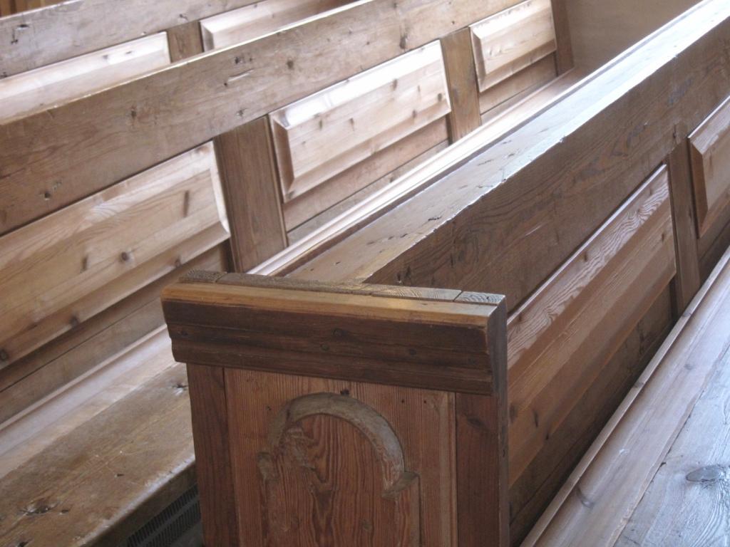 Vanhat, patinoituneet kirkon puupenkit.